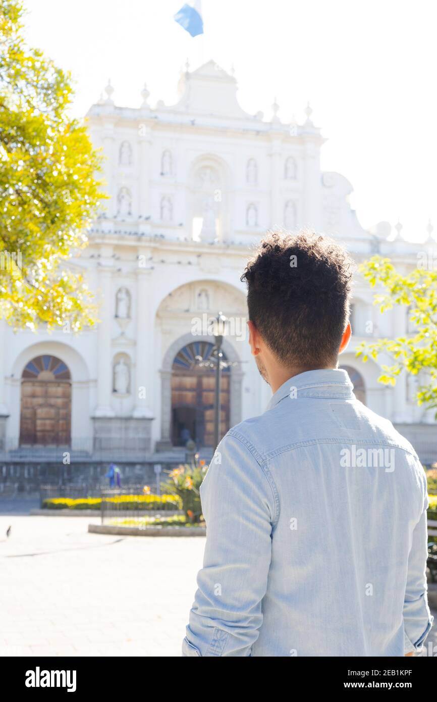 Hispanic young man standing in front of the San Jose cathedral in Antigua Guatemala - young tourist observing the church architecture in the colonial Stock Photo
