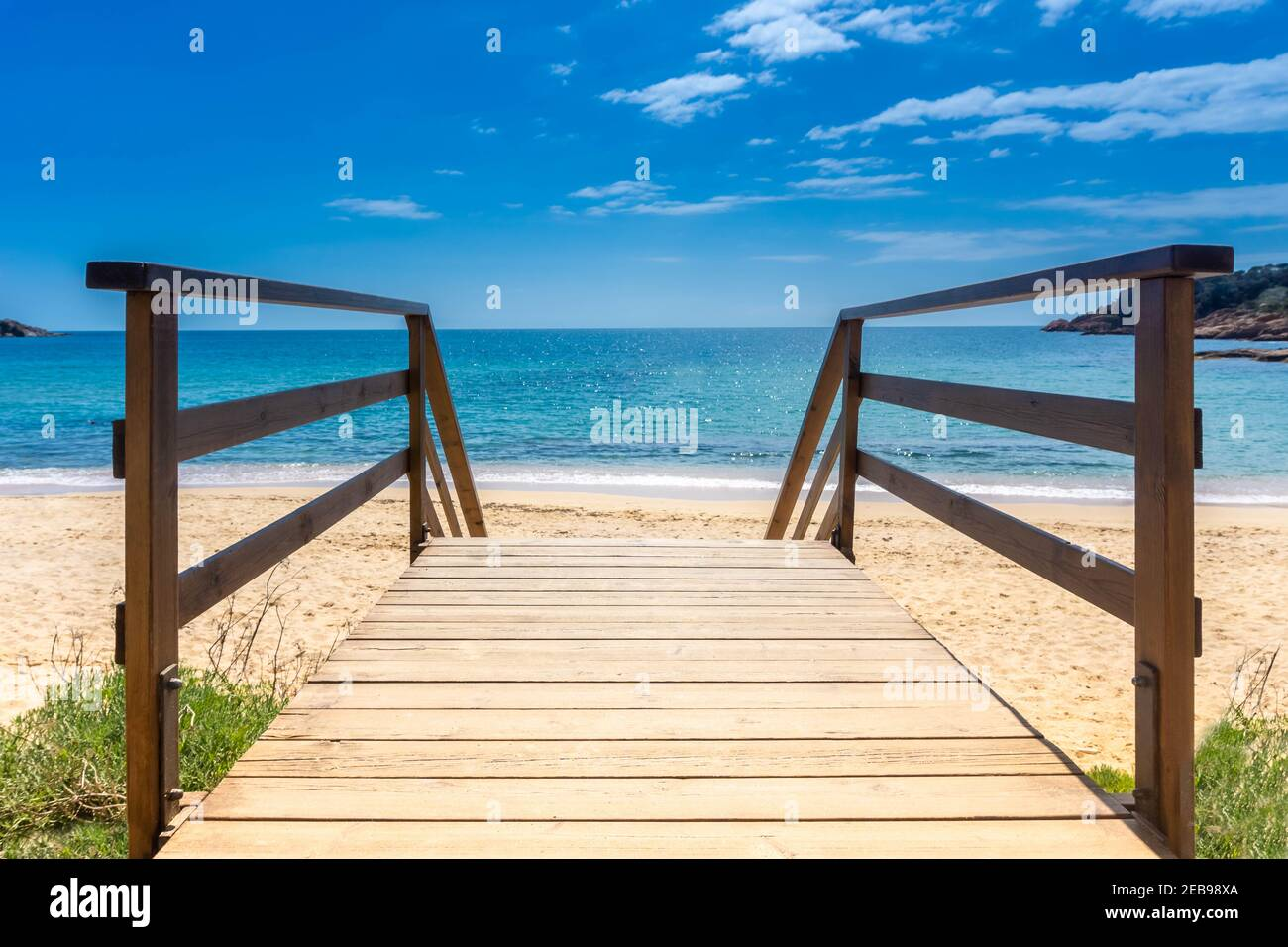 Boardwalk to sandy beach. Wooden walkway over sand to sea. Sunny beach with wooden walk floor. Vacation background. Summer vacation concept. Copy spac Stock Photo