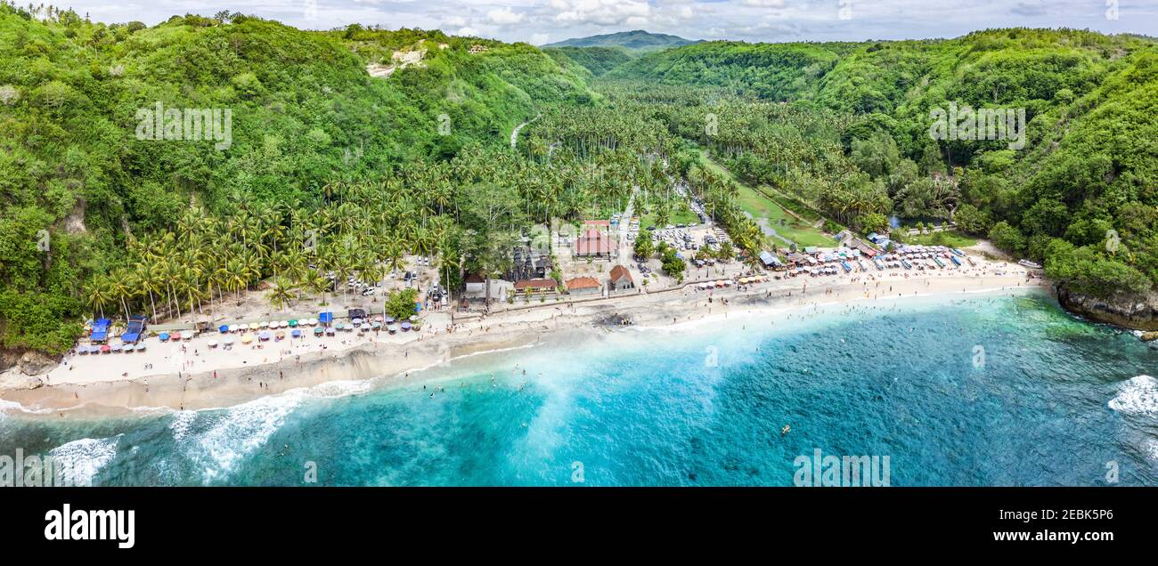 Magnificent aerial panorama of tropical beach at end of mountain valley with coconut palms, boats in blue water in Ocean gulf, unrecognized people Stock Photo