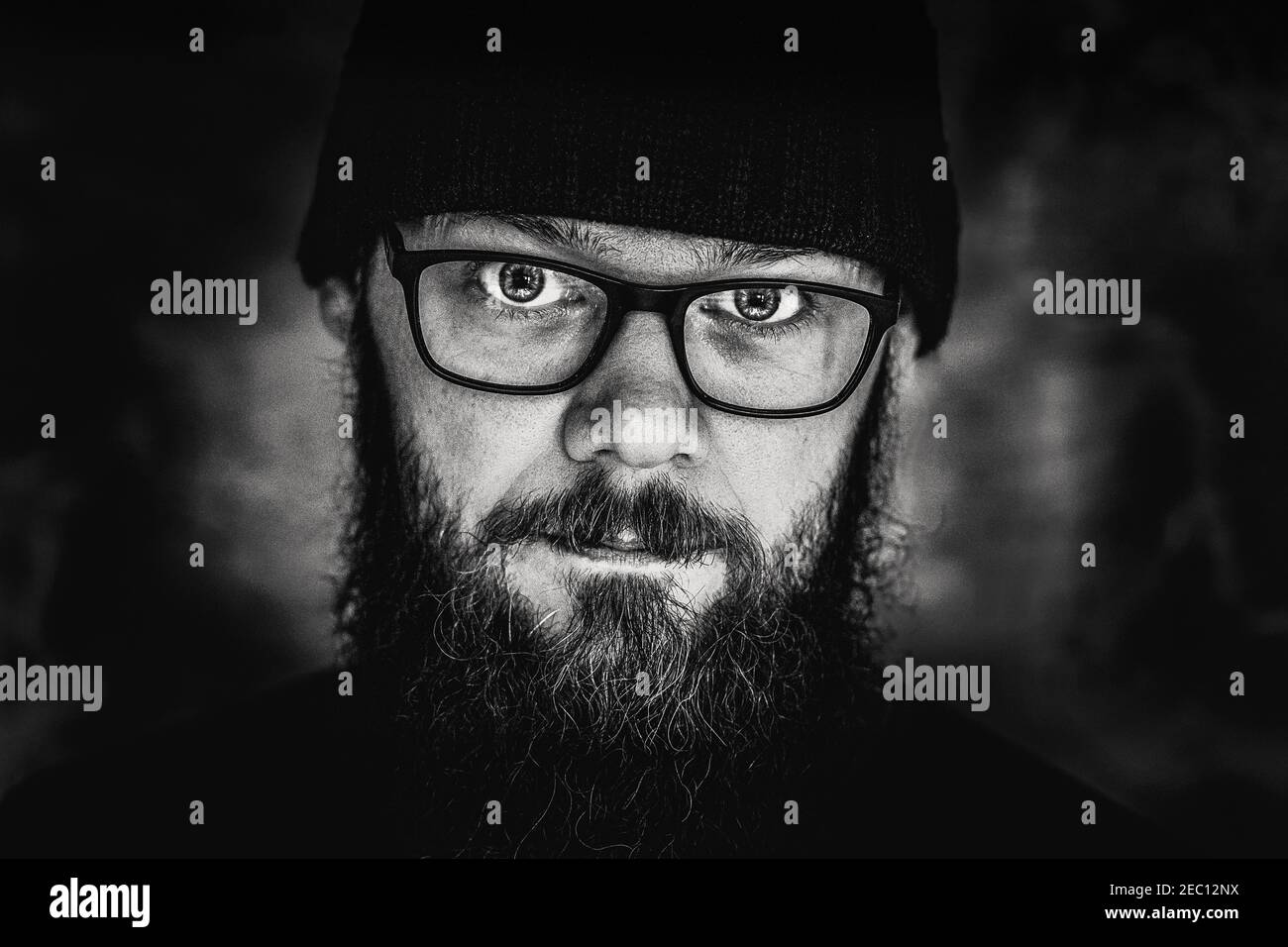 black and white portrait of a man with a beard and glasses, close-up, studio Stock Photo