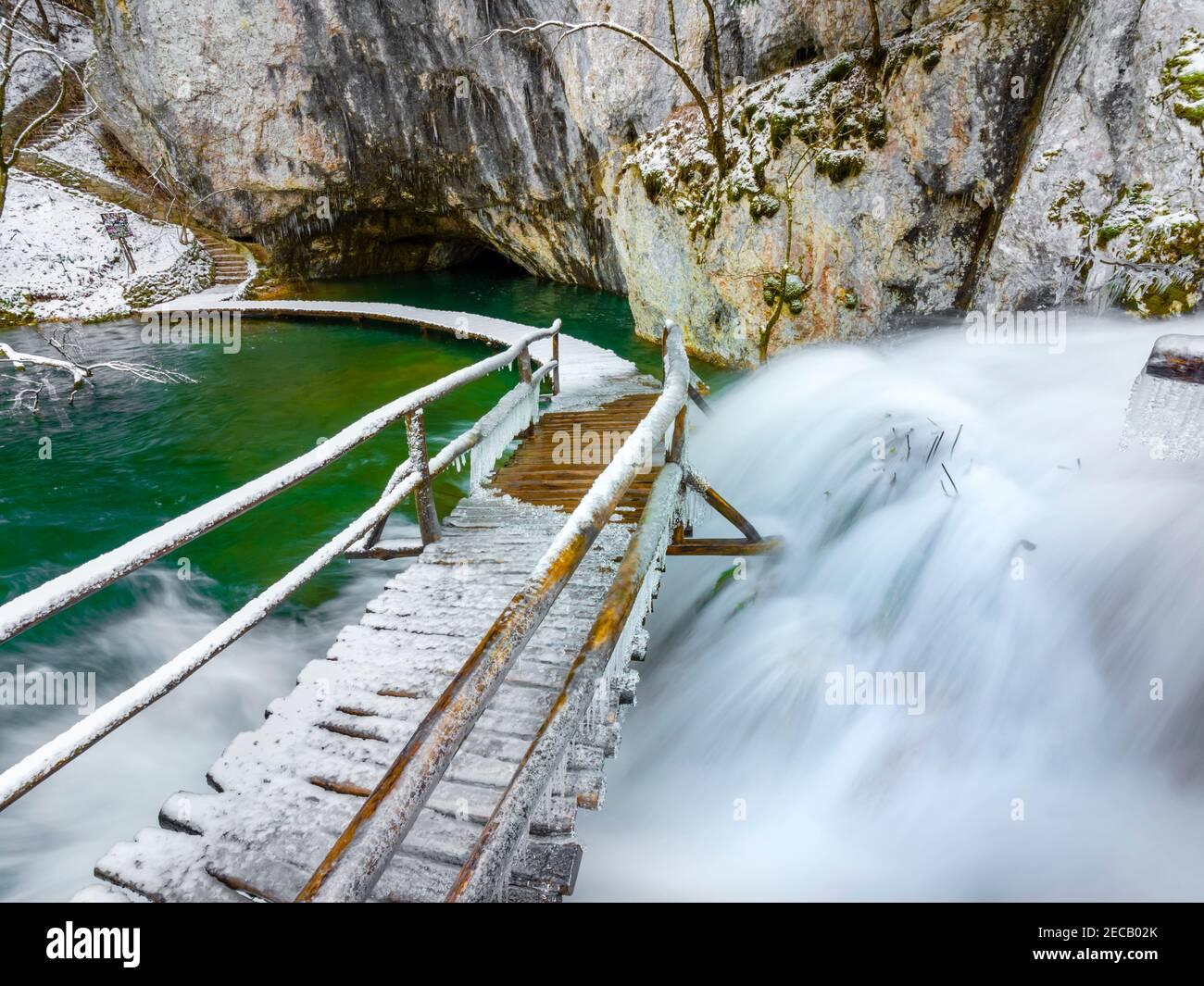 Massive water flow Plitvice lakes Croatia Europe Winter under covered cover snow ice waterflow water flowing flow overwater bridge footbridge Stock Photo