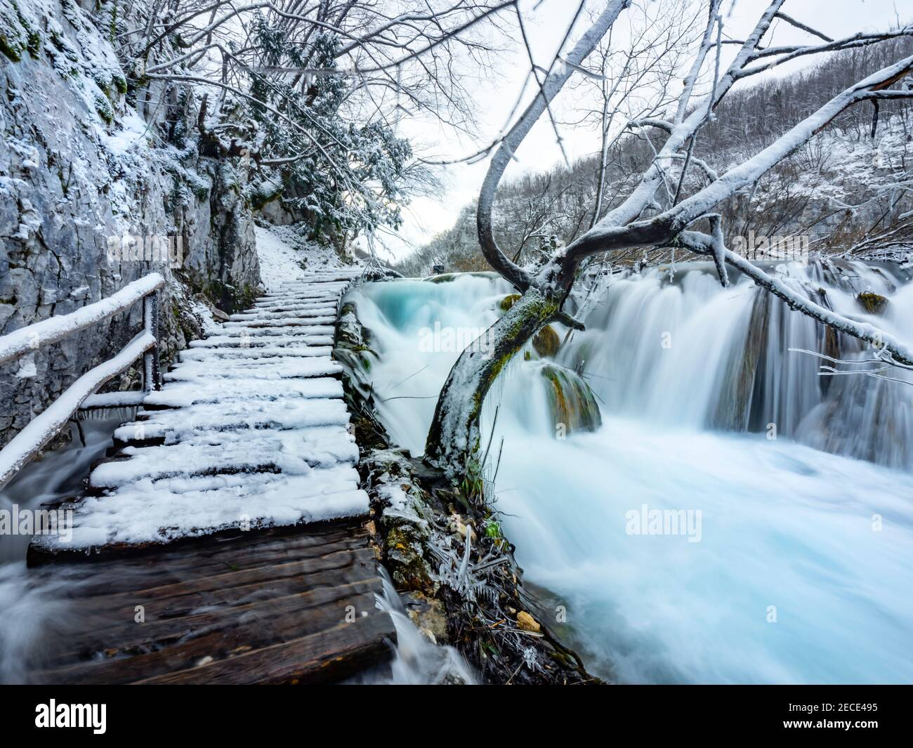 Frozen national park Plitvice lakes Croatia Europe Winter under covered cover snow ice waterflow flowing flow wooden walkway trail path trailparh Stock Photo