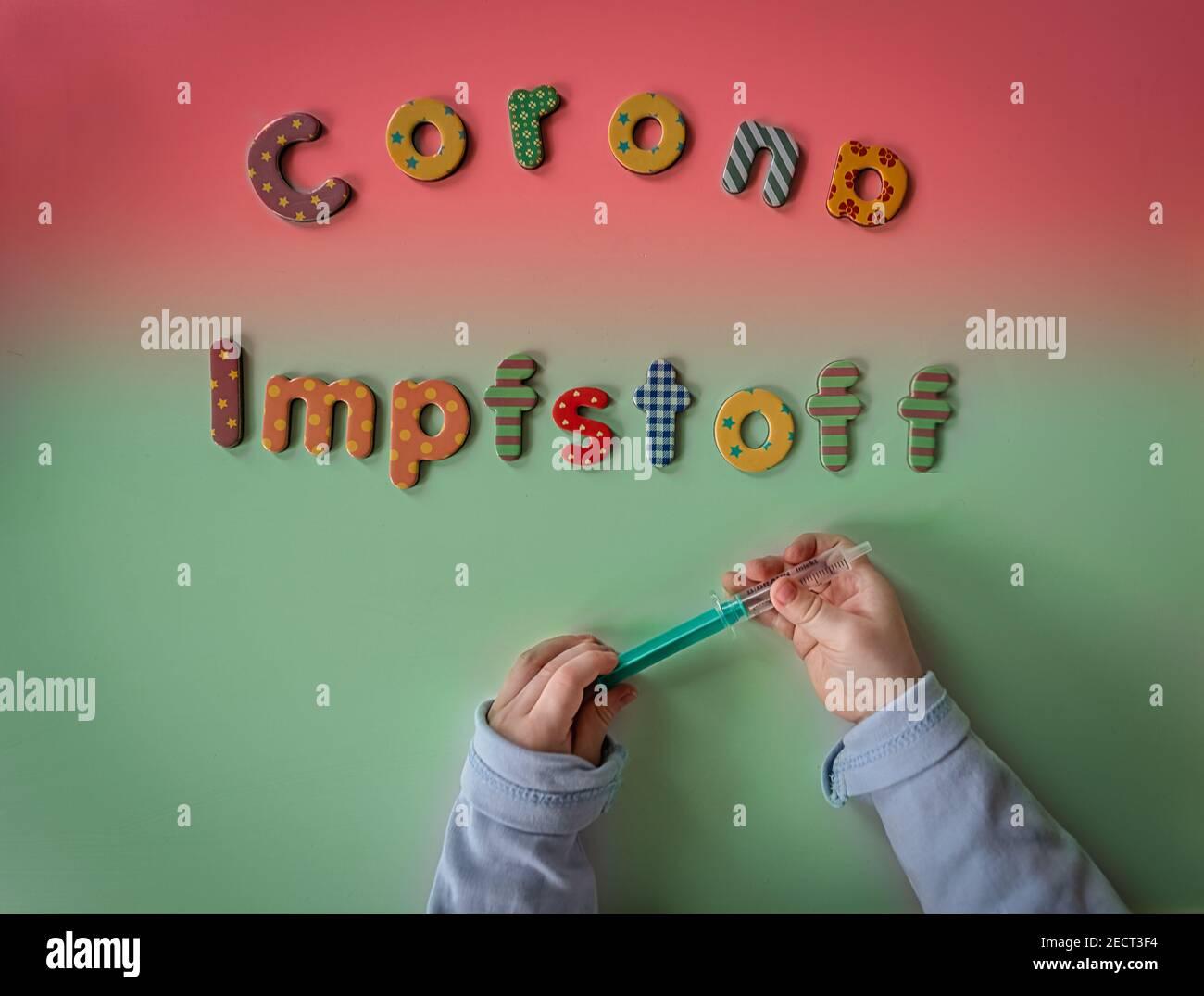 Corona Impfstoff in Buchstaben und mit einer Spritze von Kinderhaenden gehalten als Zeichen der Hoffnung in Panemiezeiten von Corona bzw. Covid-19. Stock Photo