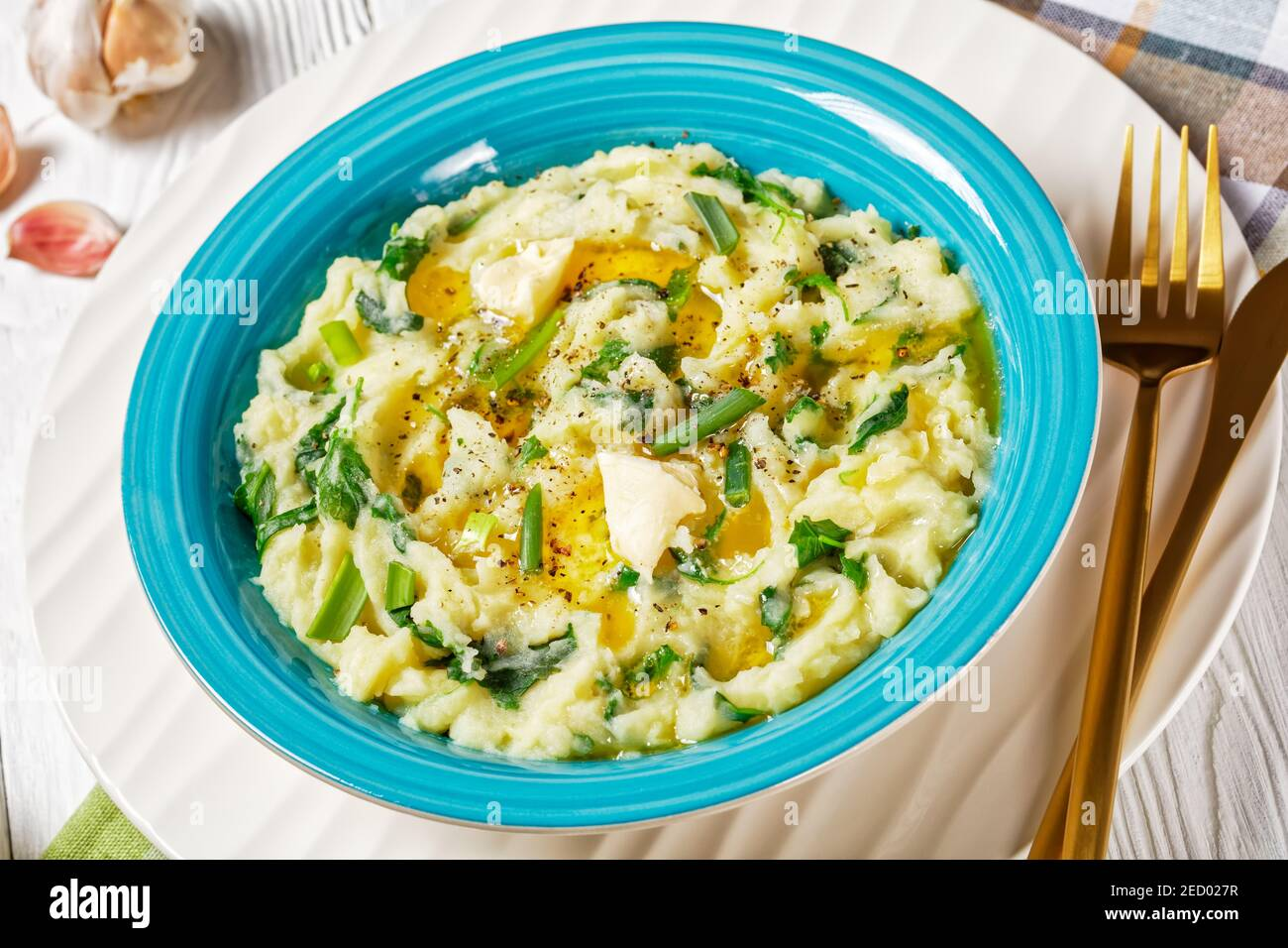 Irish colcannon traditional potato mash with kale, garlic, melted butter and spring onion served on a blue bowl, white counter plate on a white wooden Stock Photo