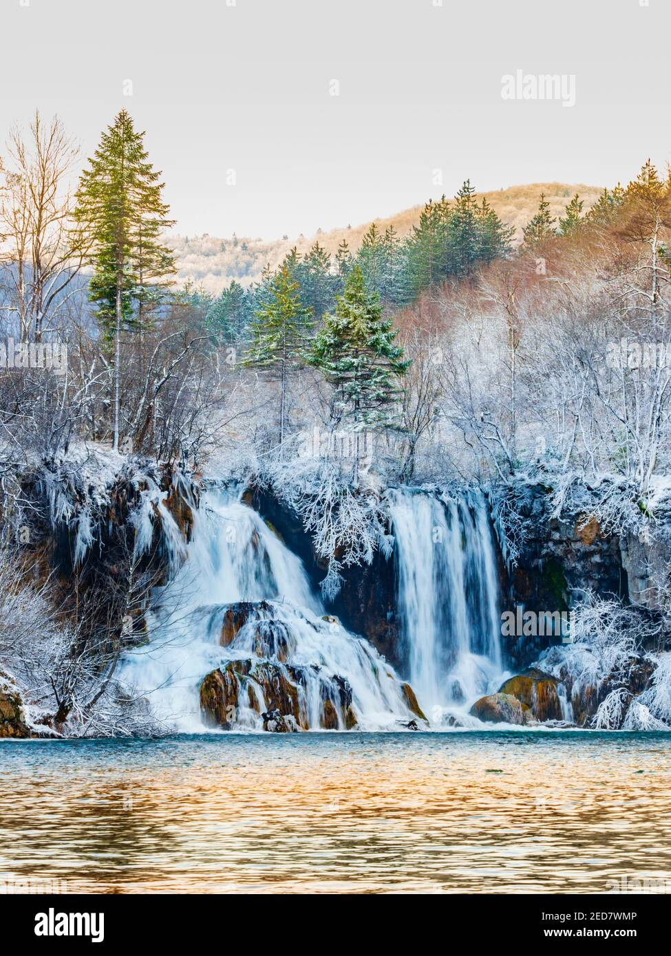 Morning warm light waterfalls waterfall national park Plitvice lakes Croatia Europe Winter under covered cover snow ice waterflow water flowing flow Stock Photo