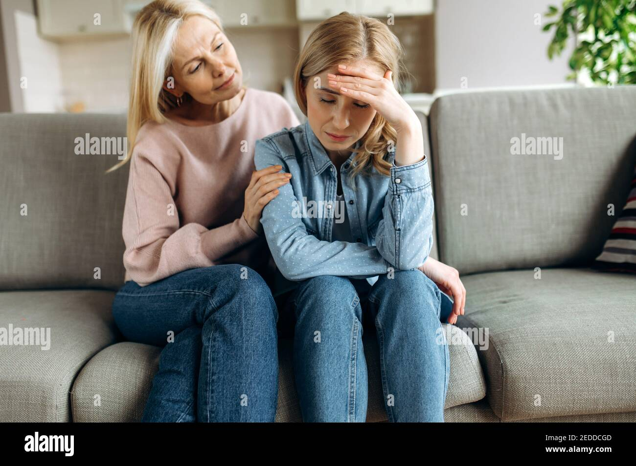Worried mature mother consoles her adult daughter, helping with problem and depression, caring she, empathy, support in two age generations. Support of a loved one Stock Photo