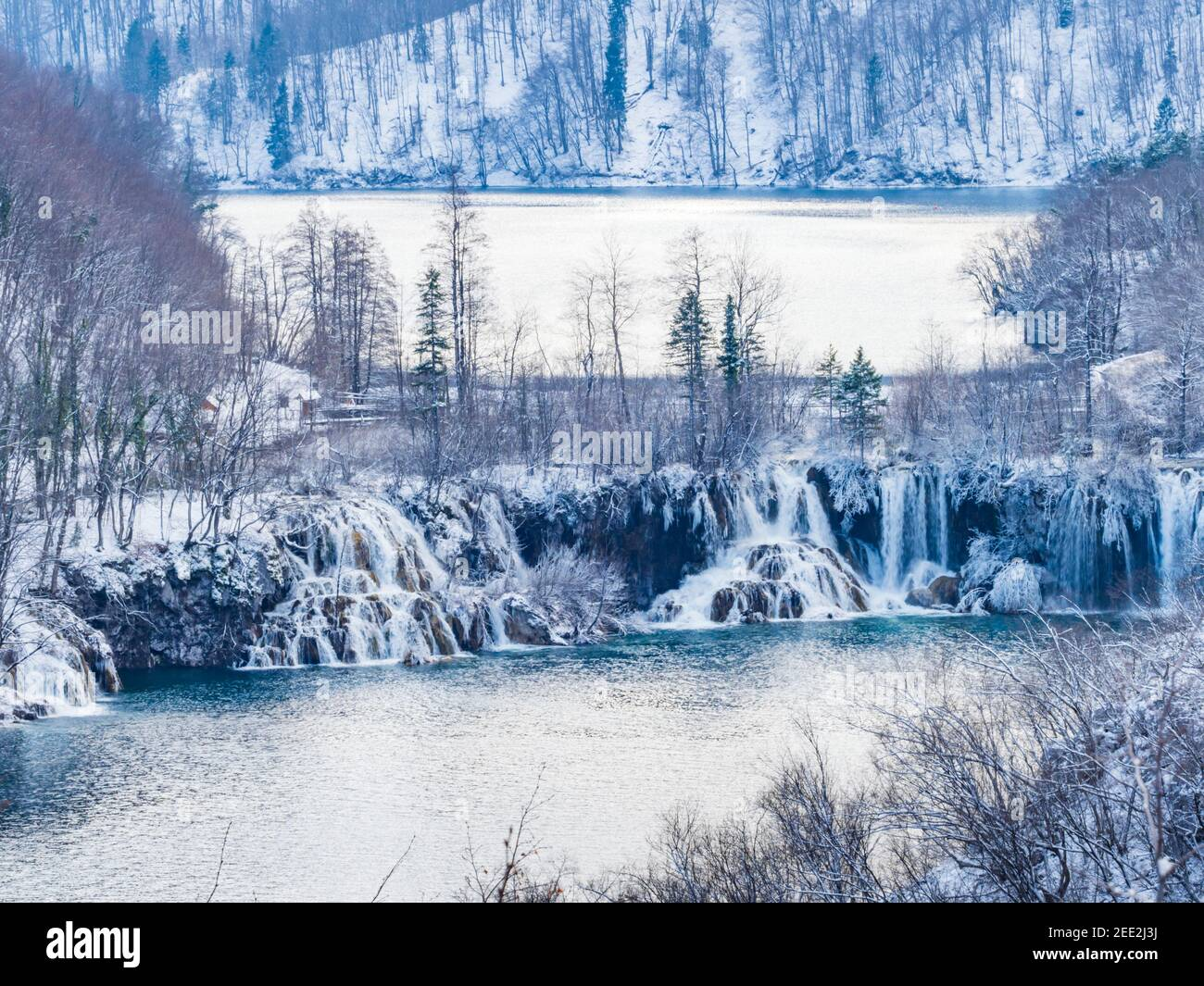 Small cascading waterfalls in national park Plitvice lakes Croatia Europe Winter under covered cover snow ice waterflow water flowing flow Stock Photo