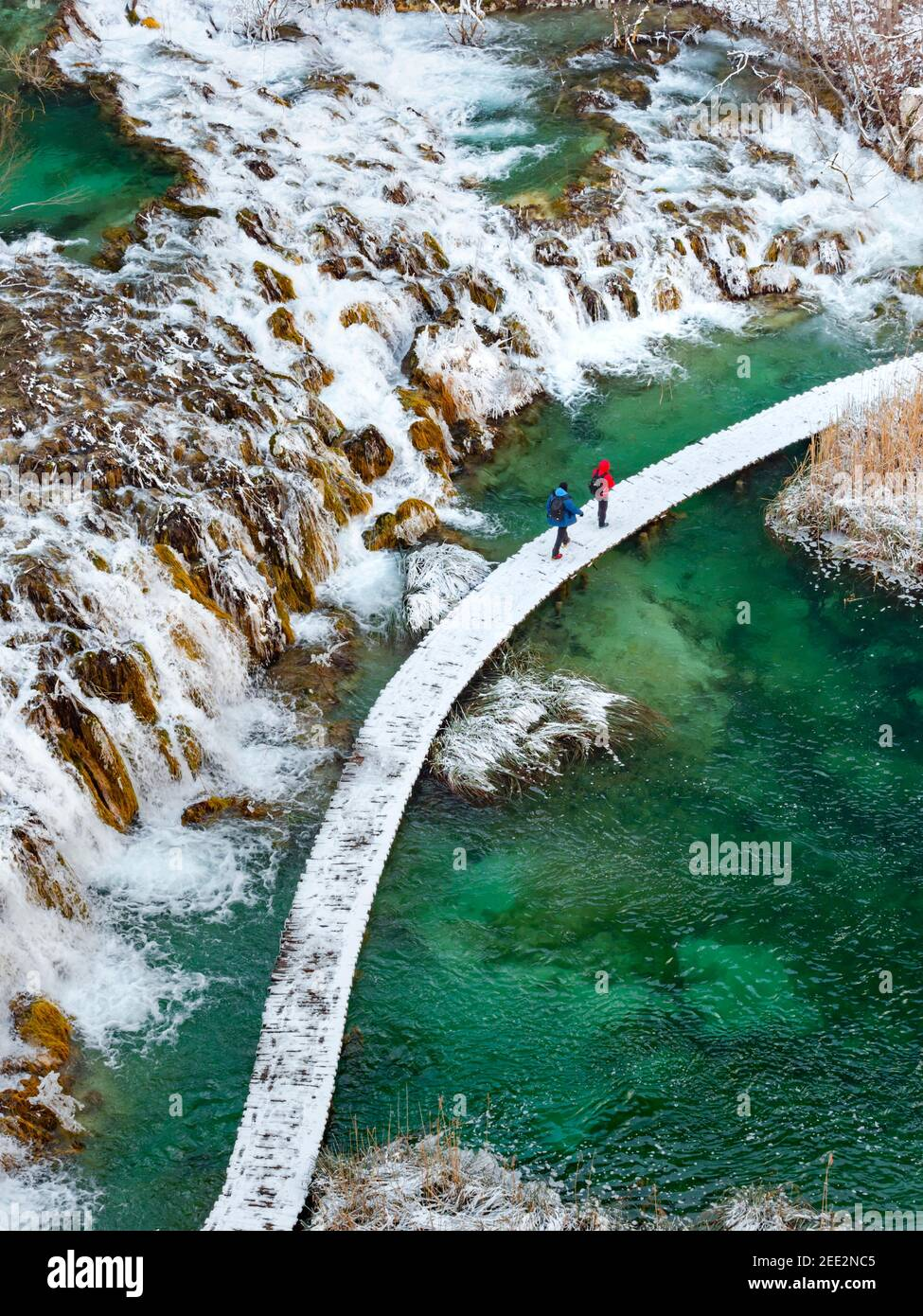 Two visitors human person persons people inational park Plitvice lakes Croatia Europe Winter under covered cover snow ice waterflow water flowing flow Stock Photo