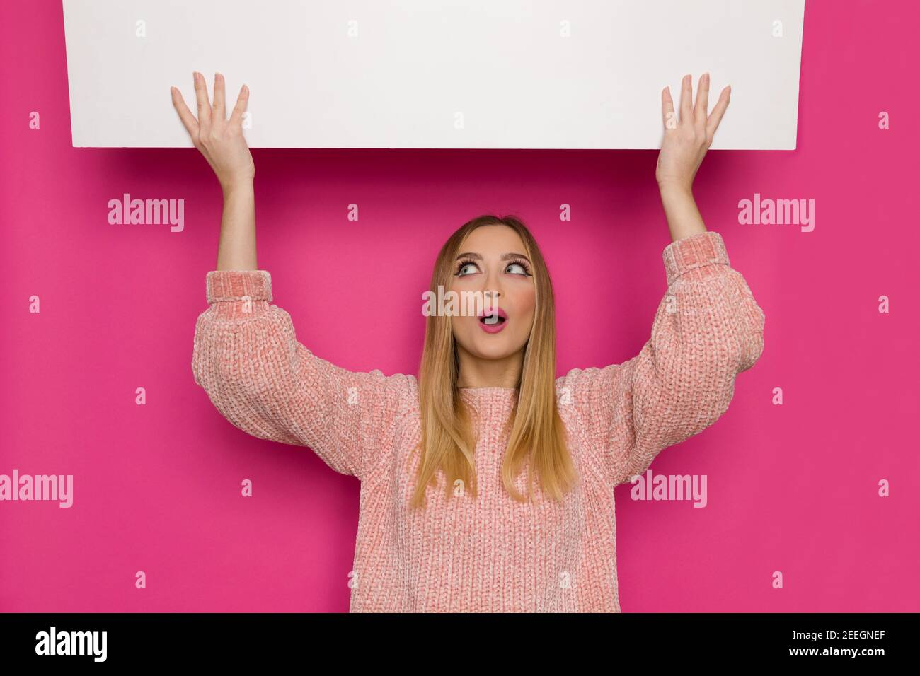 Surprised young woman in pink sweater is holding white banner over head, looking up and talking. Front view. Waist up studio shot on pink background. Stock Photo