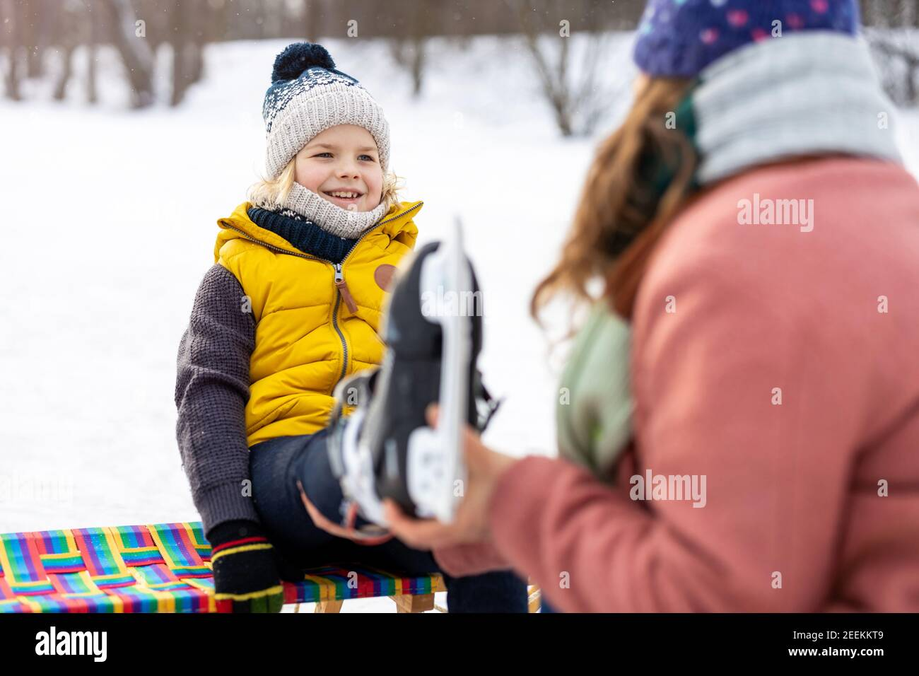 Mother helping son to put on his ice skates Stock Photo