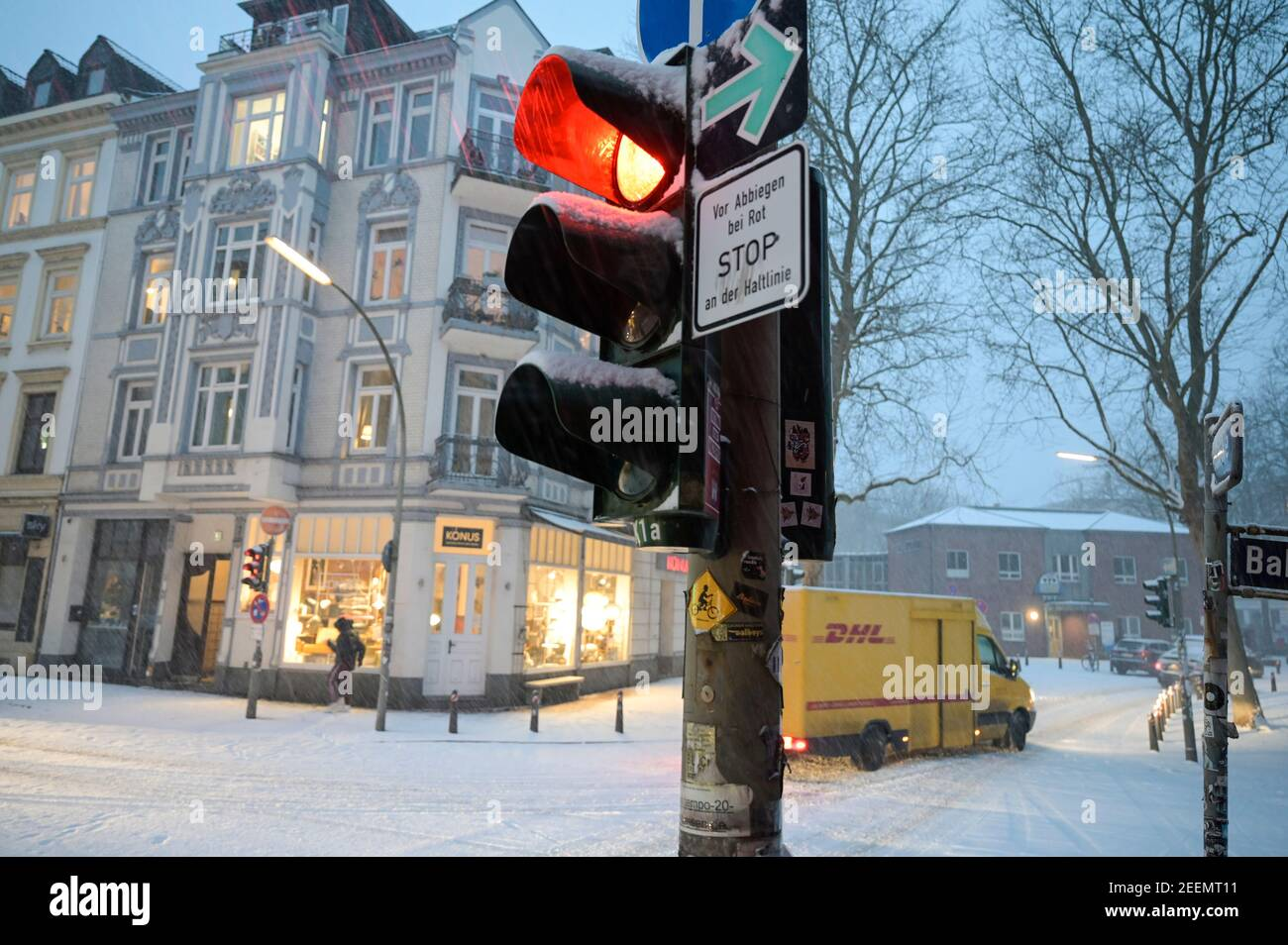 GERMANY, Hamburg, winter, snow, red traffic light, yellow DHL vehicle, parcel delivery service Stock Photo