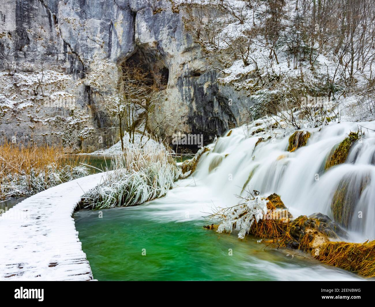 Wooden walkway trail path trailparh promenade in Plitvice lakes Croatia Europe Winter under covered cover snow ice waterflow water flowing flow Stock Photo