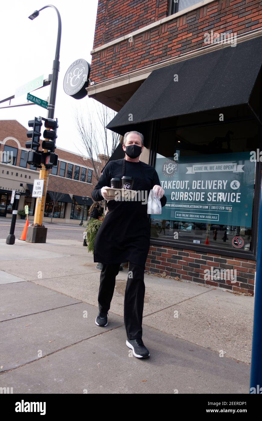 Curbside service by masked and gloved waitperson bringing coffees and pastries to the car from Bread and Chocolate cafe. St Paul Minnesota MN USA Stock Photo
