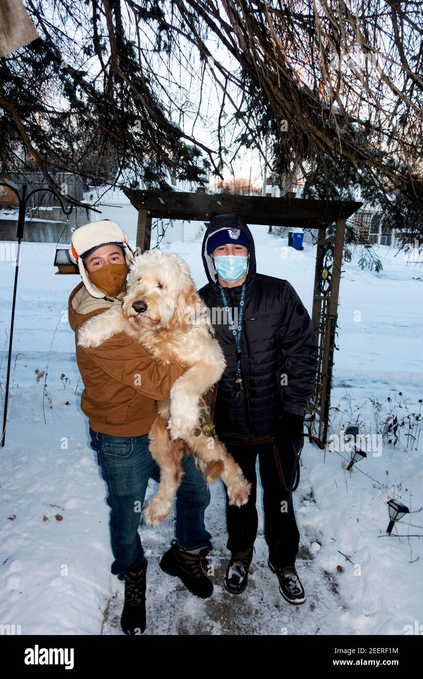 Brothers with their Goldendoodle pet dog coming to visit grandma and grandpa outside wearing masks during the Covid Pandemic. St Paul Minnesota MN USA Stock Photo
