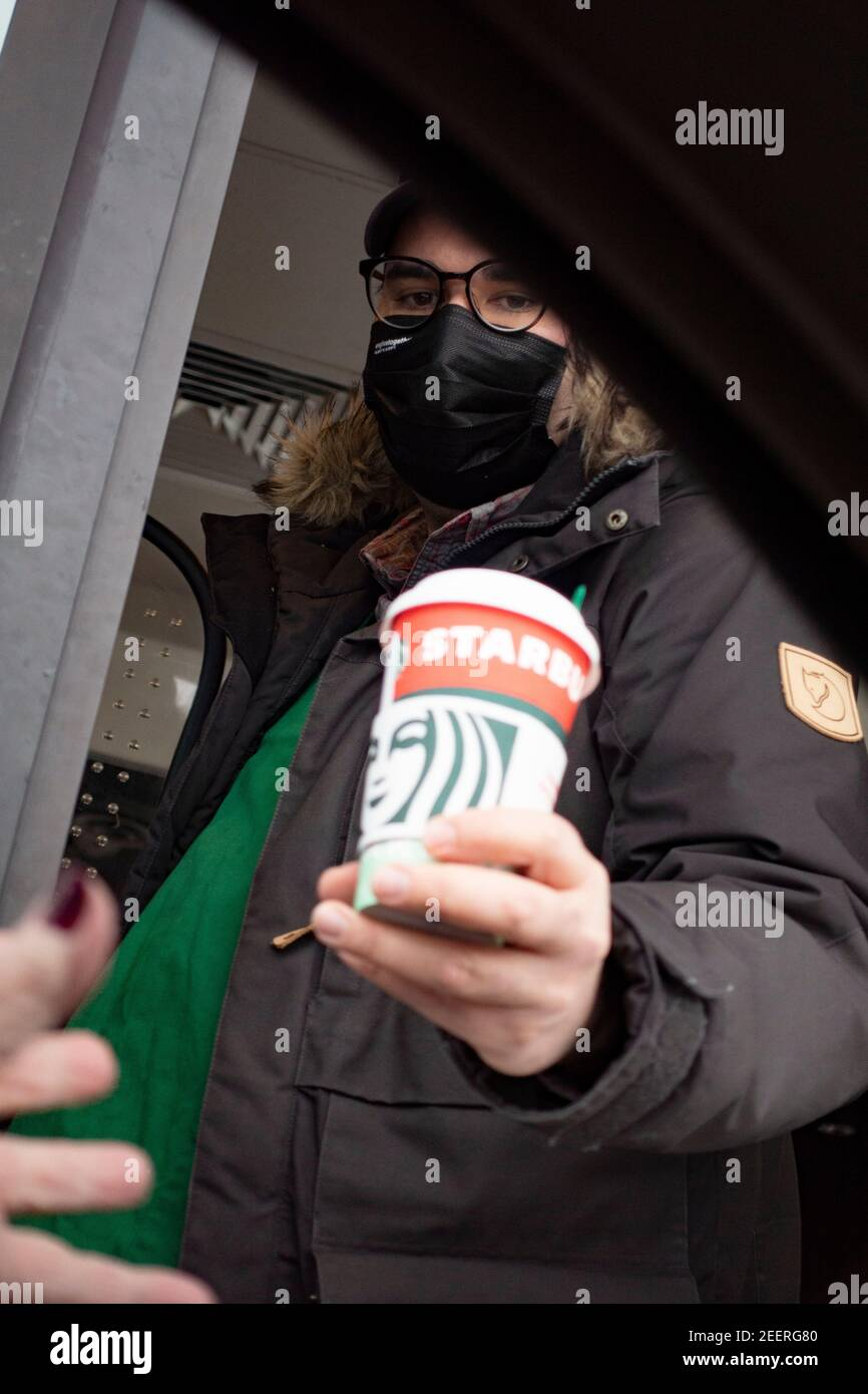 Masked coffee server handing a cup to a customer in a car at Starbucks drive-thru. St Paul Minnesota MN USA Stock Photo