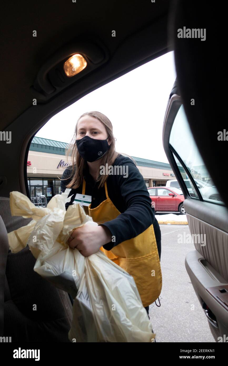 Lunds & Byerlys supermarket shopper masked loading groceries in customer's car curbside online service during Covid Pandemic St Paul Minnesota MN USA Stock Photo