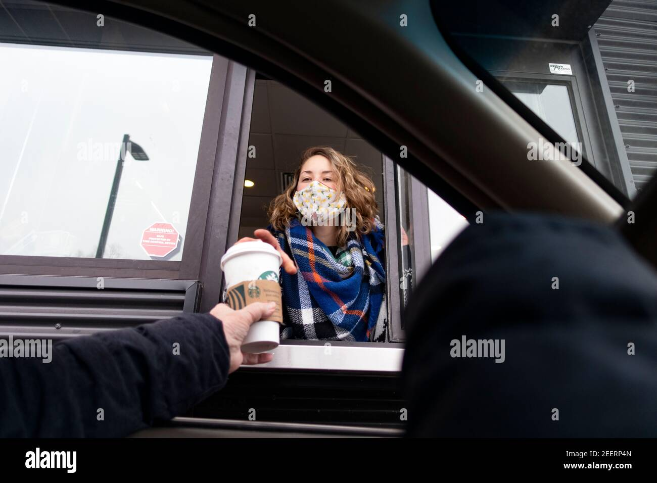 Masked Starbucks drive-thru coffee server handing a coffee to a customer in the car during the Covid Pandemic. St Paul Minnesota MN USA Stock Photo