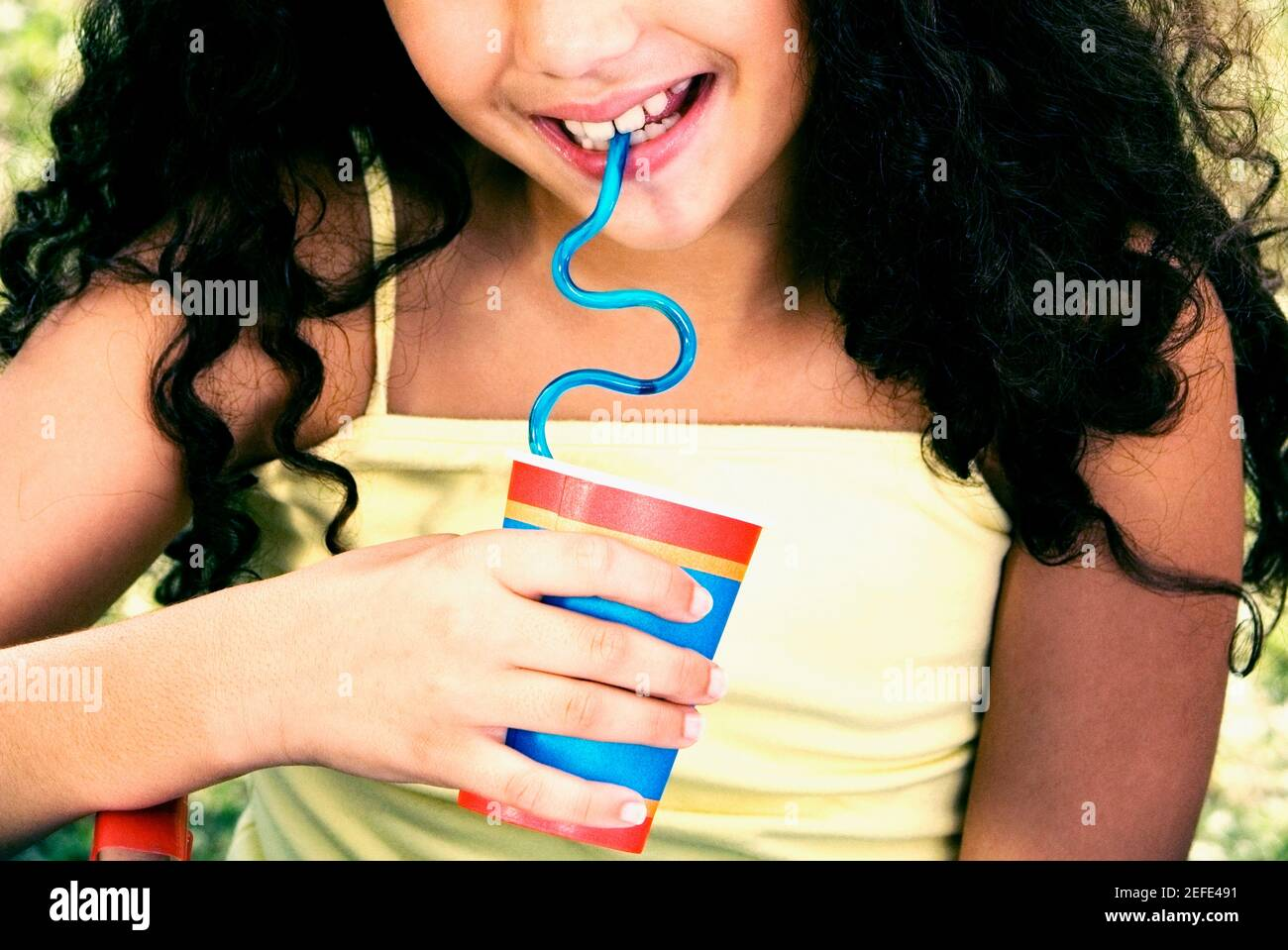 Close-up of a girl holding a disposable cup and drinking with a straw Stock Photo