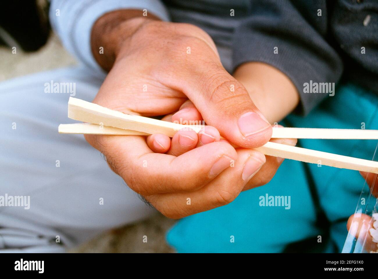Close-up of a father teaching his son the use of chopsticks, Okinawa, Japan Stock Photo