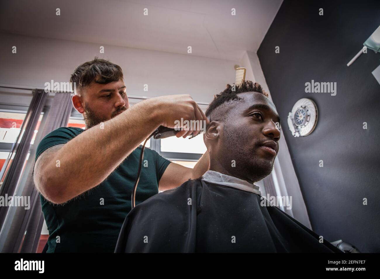 a young African boy gets his hair cut by his barber Stock Photo