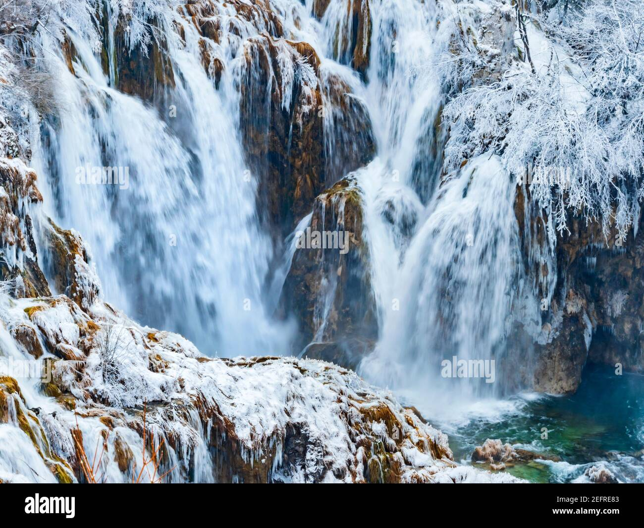 Dynamic Winter season waterfalls in Plitvice lakes Croatia Europe with snow ice waterflow flowing flow atop rocky rough terrain sprinkling water Stock Photo