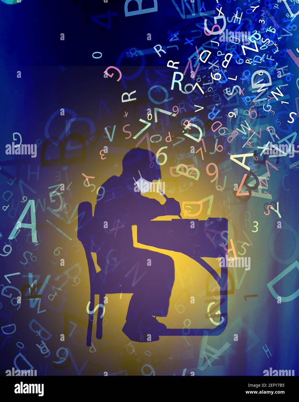 schoolboy wearing mask sitting at desk surrounded by letters Stock Photo