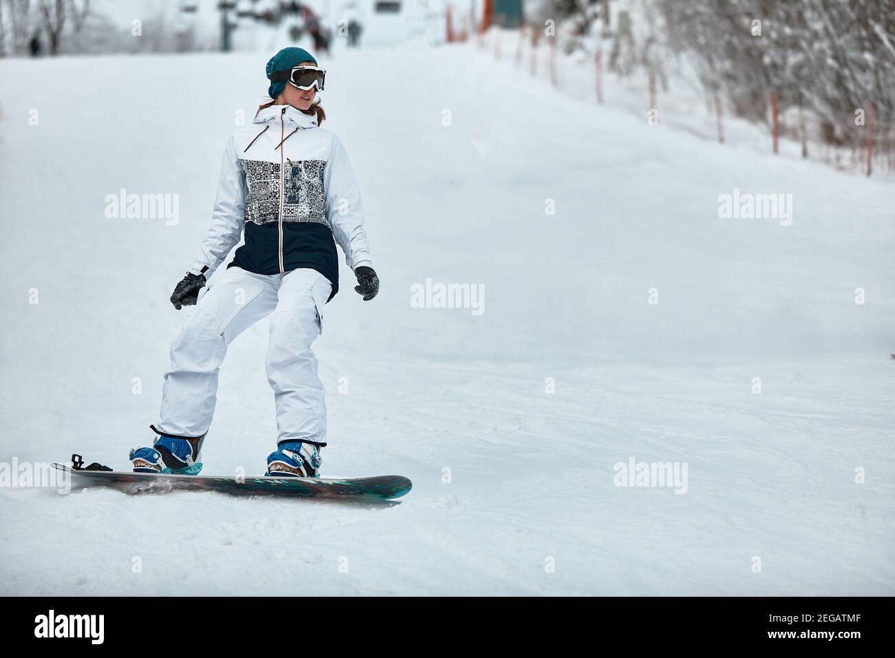 cheerful woman riding on snowboard in the mountains in winter. woman in white ski suit. Stock Photo