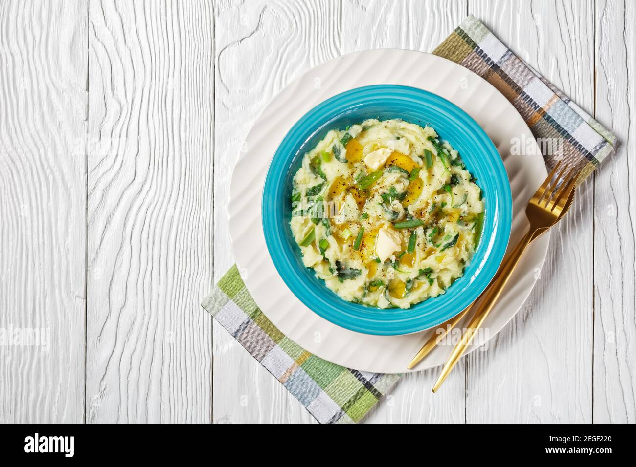 Creamy irish colcannon traditional potato mash with kale, garlic, melted butter and spring onion served on a blue bowl with cutlery on a white wooden Stock Photo