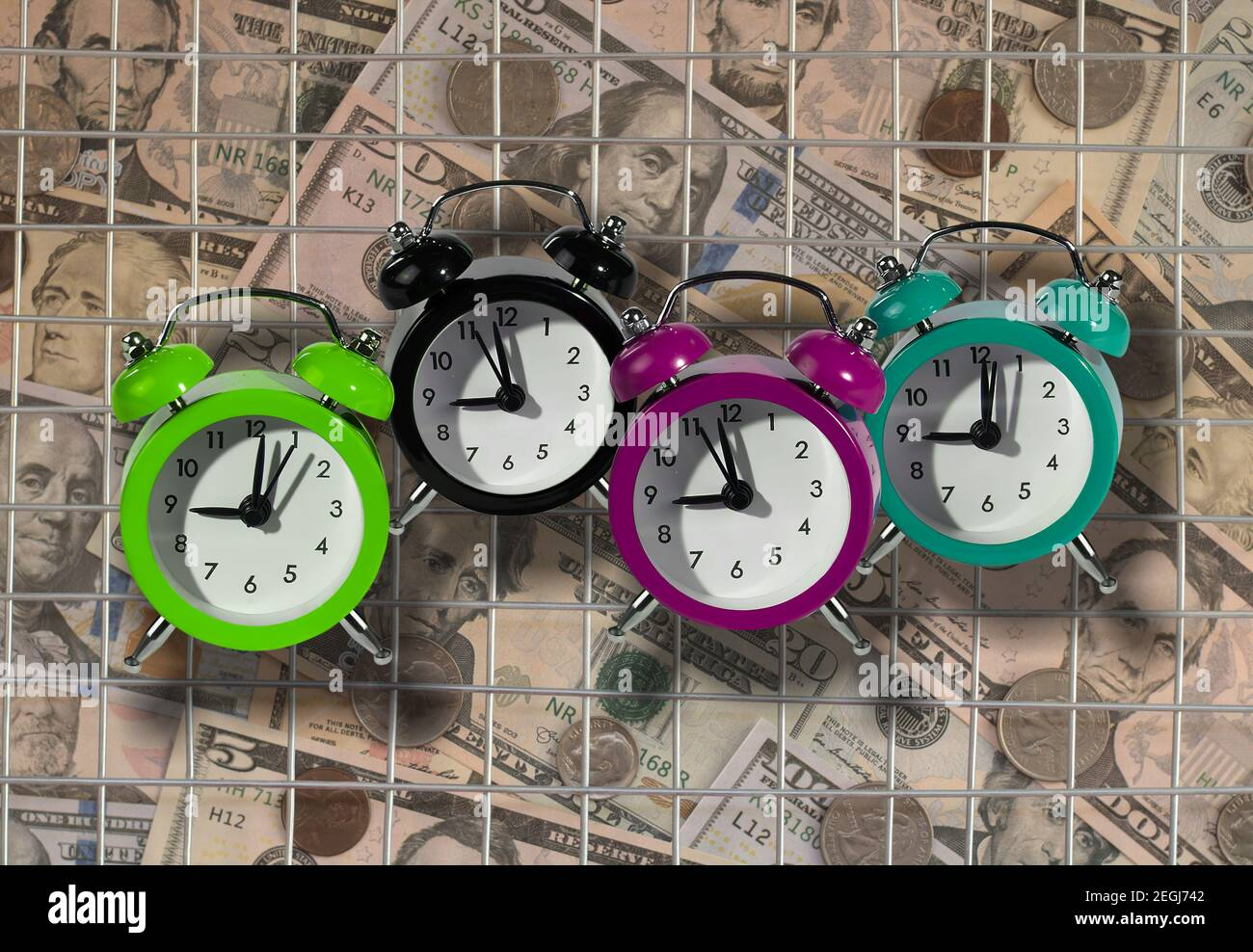 Alarm clocks as a tax reminder symbol. Bars as a symbol of prison for unpaid tax on time or hiding income from the Tax Office. Stock Photo