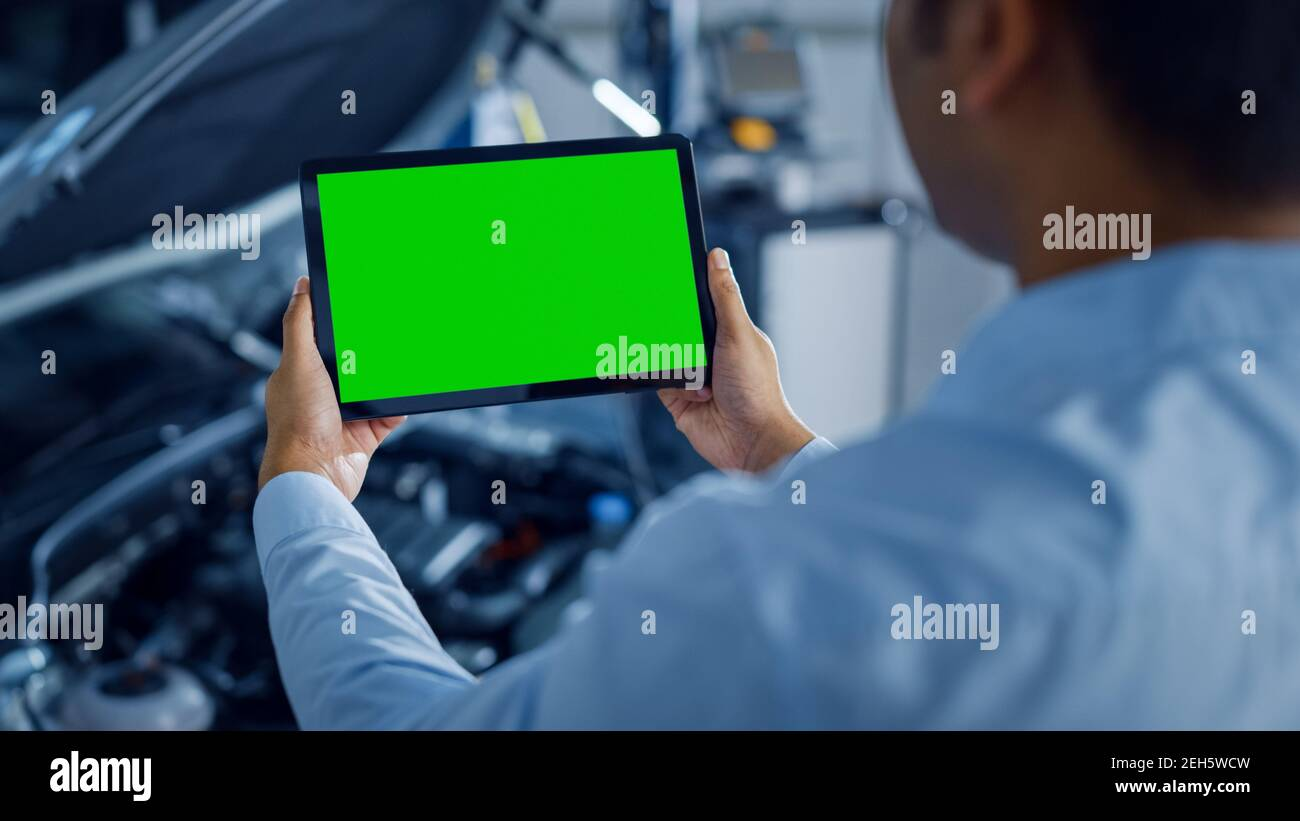Car Service Manager or Mechanic Uses a Tablet Computer with a Green Screen Mock Up that is Pointed at an Enginer Bay. Specialist Inspecting the Stock Photo
