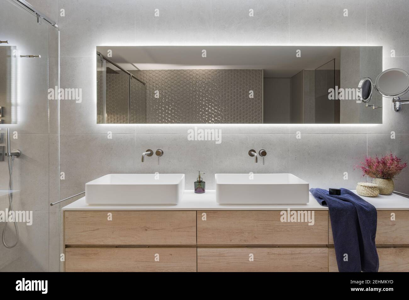 Modern Bathroom Interior With A Wooden Shelf Two White Sinks And Big Mirror Dark Blue Towel And Flowers For Decoration Stock Photo Alamy