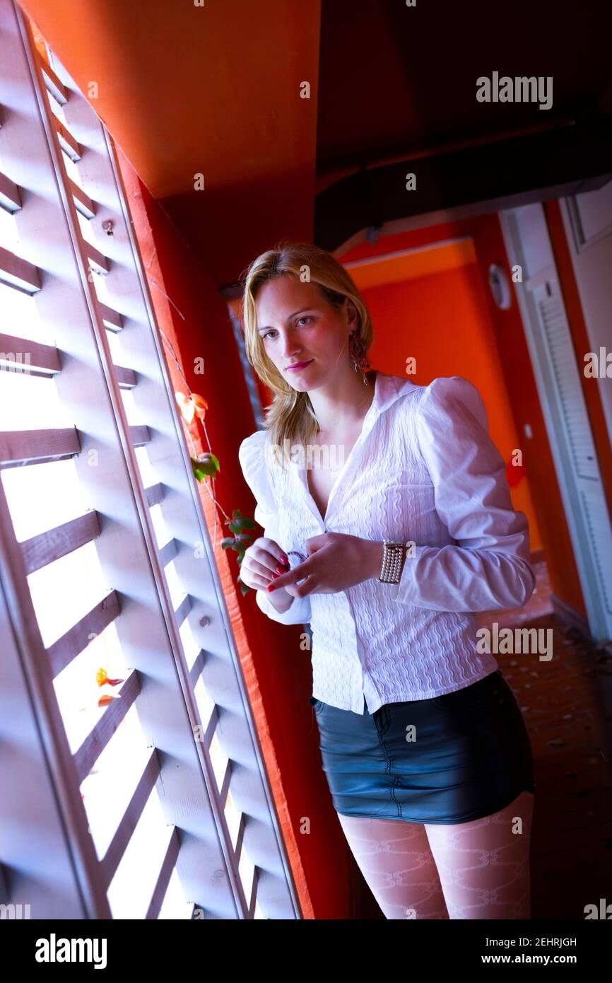 Young woman blonde blond fairhaired hair standing serious sad wait waiting looking through window venetian blinds lonesome alone Stock Photo