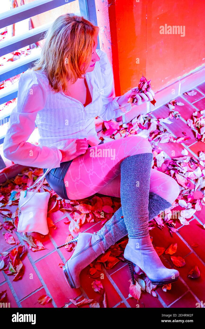 Young woman blonde blond fairhaired hair Grey Gray boots legs heels sitting seated hand hold holding grab grabbing fallen leaves altered vivid color Stock Photo