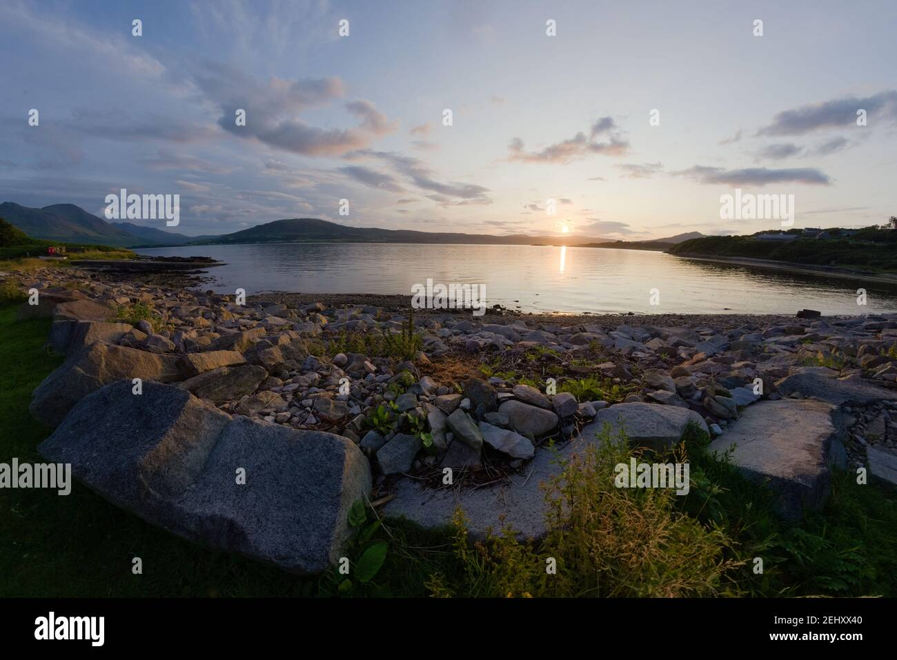A rocky boulder sea shore at sunset. Looking west near East Suisnish on the Isle of Raasay, isle of skye in the distance. A fish eye perspective. Stock Photo
