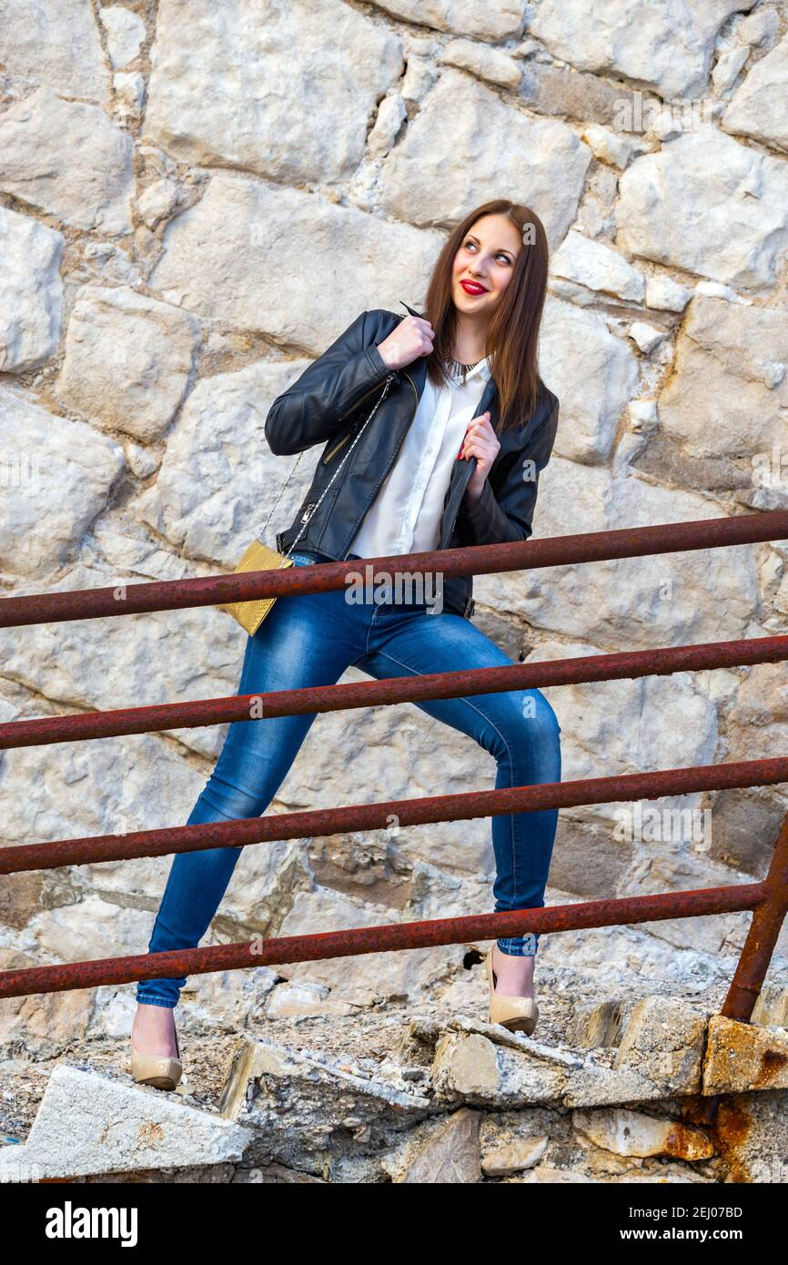 Teengirl standing wait waiting pose by rusty metal fence railing on staircase steps stairs smiling looking away aside legs heels Stock Photo