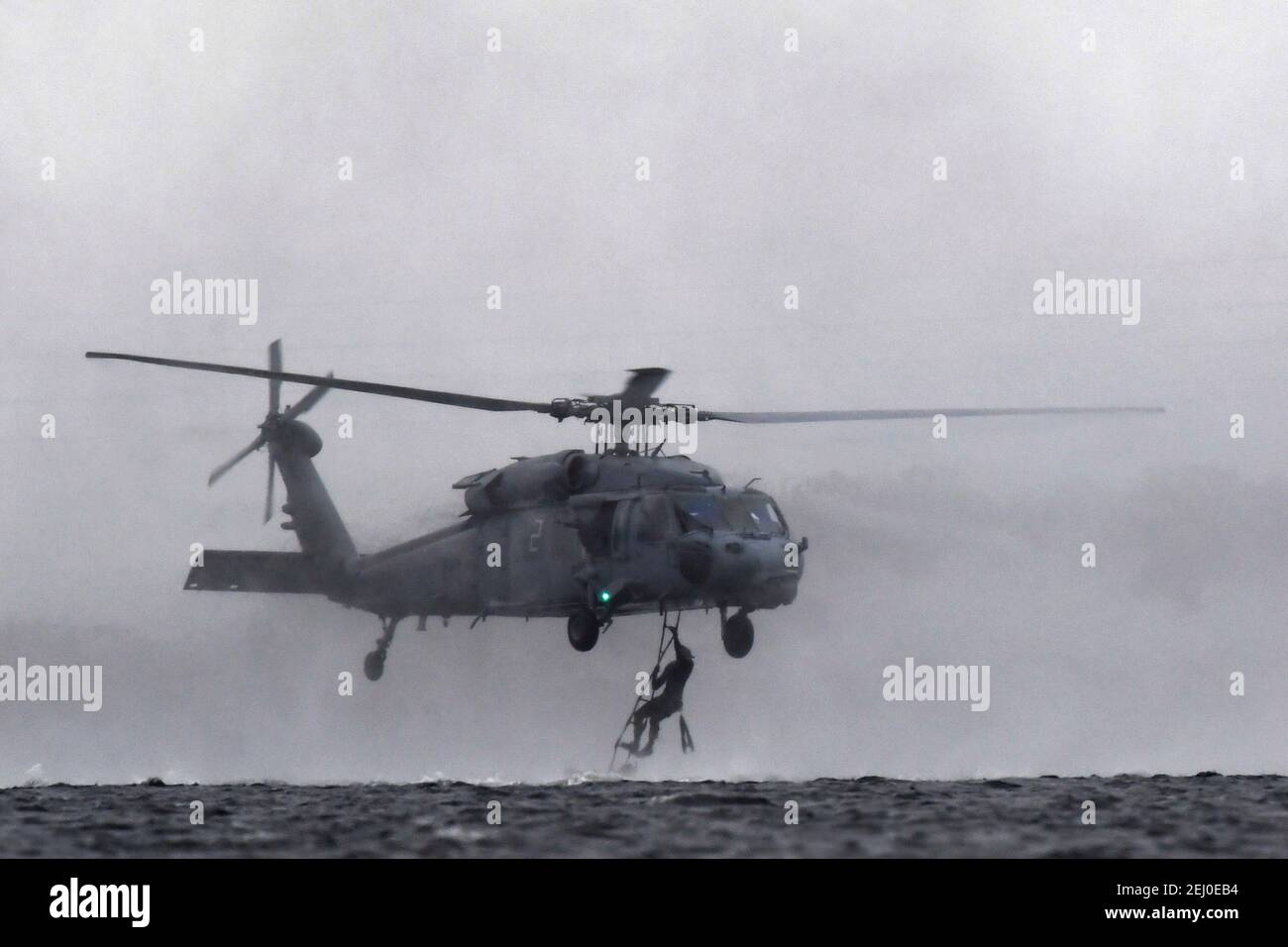 U.S. Air Force Special Tactics teams assigned to the 24th Special Operations Wing, conduct hoist operations with a Navy MH-60 Seahawk helicopter during Emerald Warrior at Hurlburt Field February 18, 2021 in Mary Esther, Florida. Stock Photo