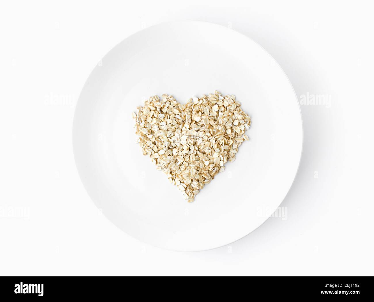 oat flakes in a shape of heart shot from above on a white plate on white background Vegetarian organic food.  Stock Photo