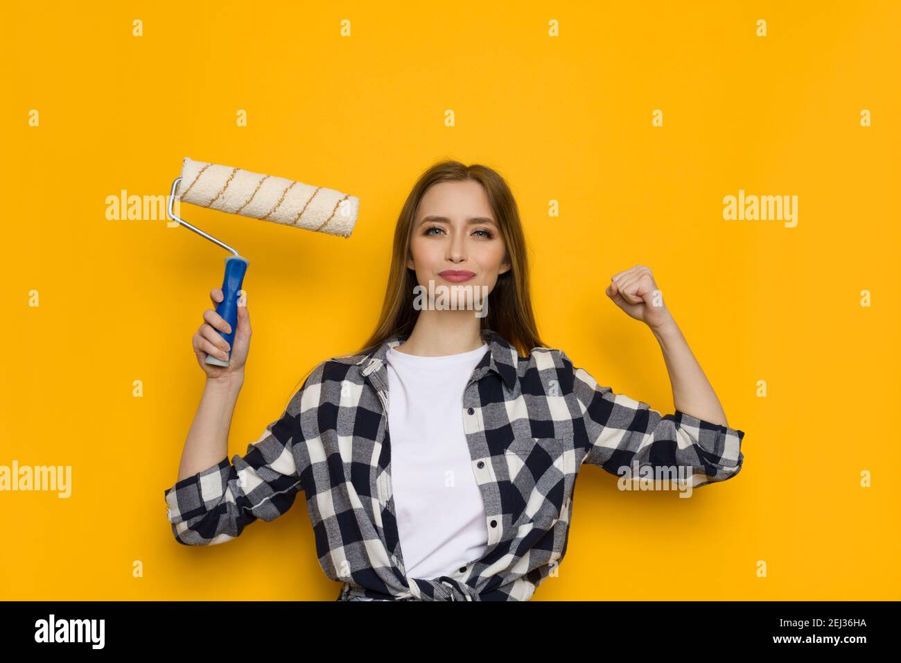 Confident casual young woman in lumberjack shirt is holding paint roller in one hand and other up with fist clenched. Waist up studio shot on yellow b Stock Photo