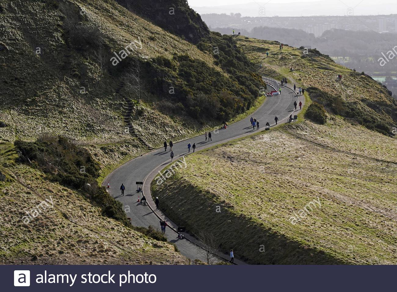 Edinburgh, Scotland, UK. 21st Feb 2021. People enjoying the sun and outdoors in Holyrood Park. People walking on Queens Drive. Credit: Craig Brown/Alamy Live News Stock Photo