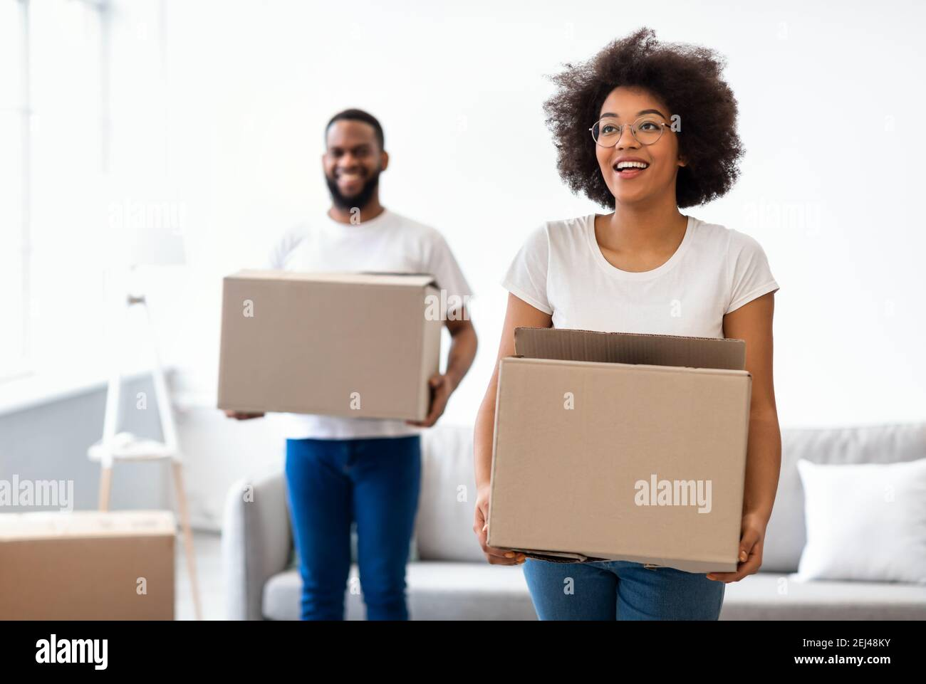 Joyful Black Spouses Carrying Moving Boxes Entering New Home Together Stock Photo