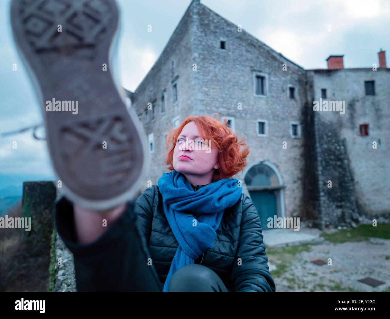 Woman with curly curls Red hair sitting before medieval fort tower high towards camera closeup under sneaker sneakers foot leg raised raising odd Stock Photo