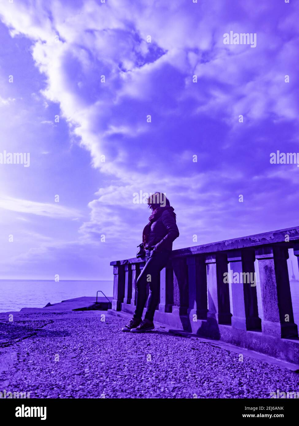 Ultra-violet UV altered creative arty artistic color woman inclined on fence waiting wait alone lonesome sunshine sunlight cloudy clouds sky Stock Photo