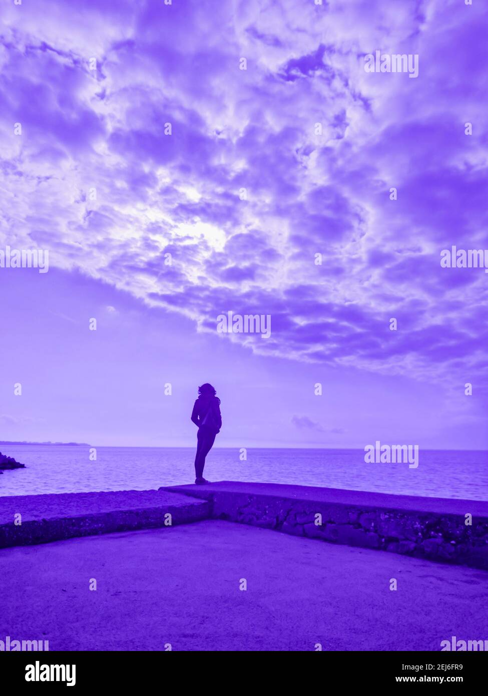 Ultra-violet UV altered creative arty artistic color woman sunshine sunlight standing od seaside near sea looking away alone lonesome Stock Photo