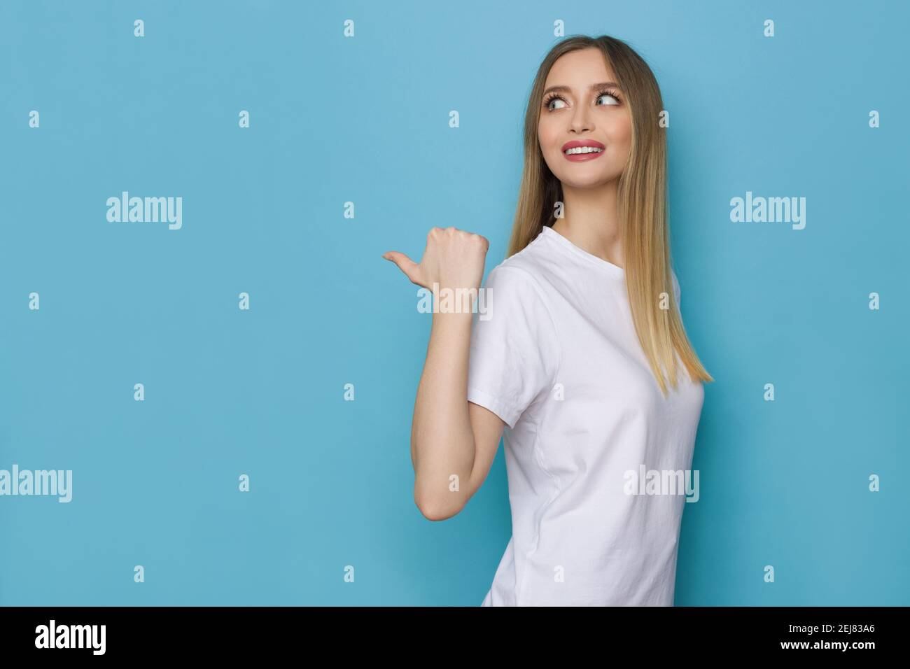 Smiling young woman in white shirt is pointing behind herself with thumb and looking away. Side view. Waist up studio shot on blue background. Stock Photo
