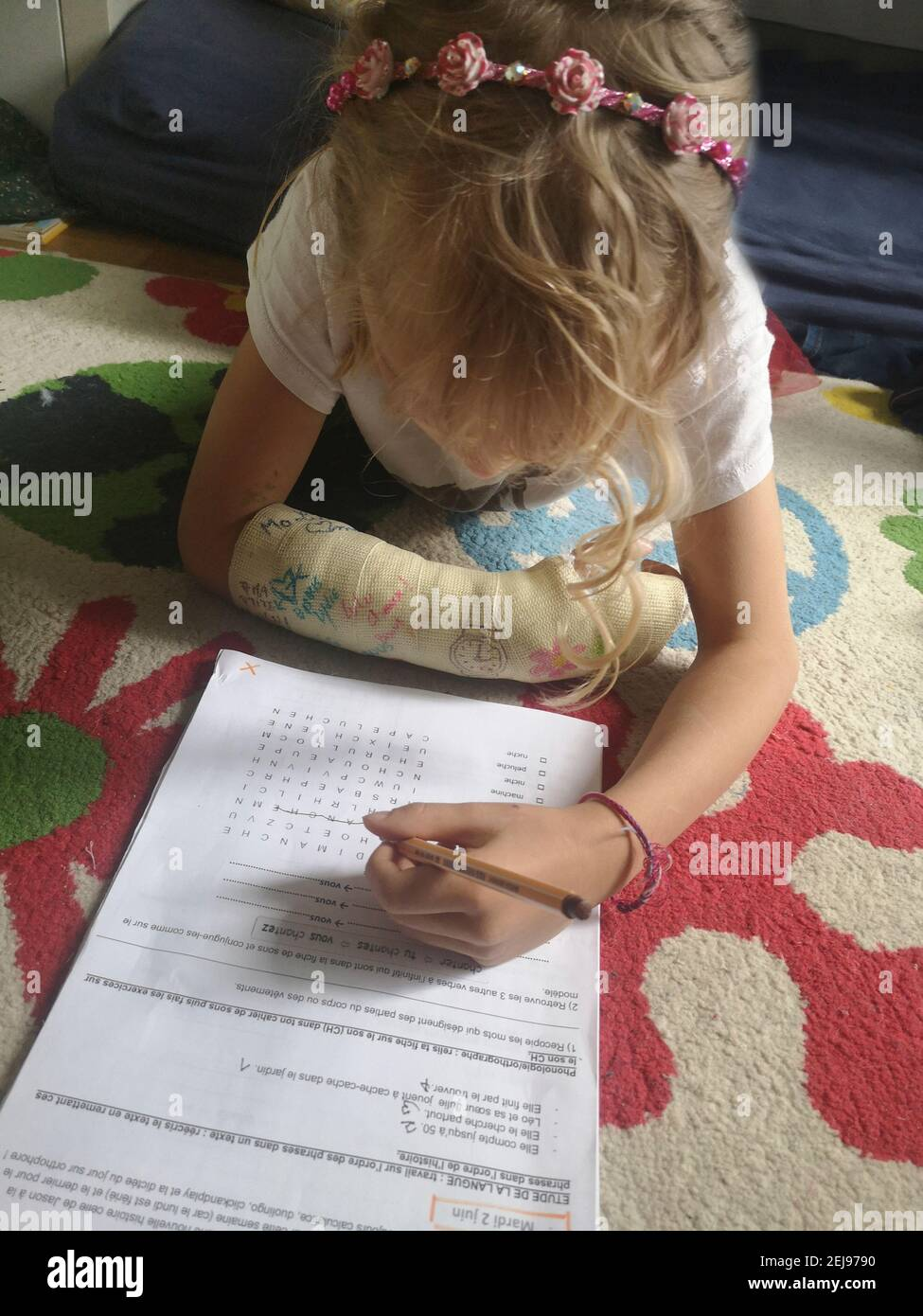 7-9 year old European girl with a plastered broken arm doing her homework with her left hand, France. Stock Photo