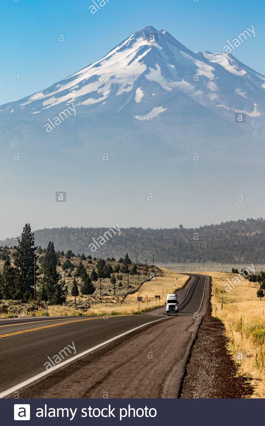 Mount Shasta and trucks along rural highway - Grass Lake, Weed, California, United States (US) Stock Photo