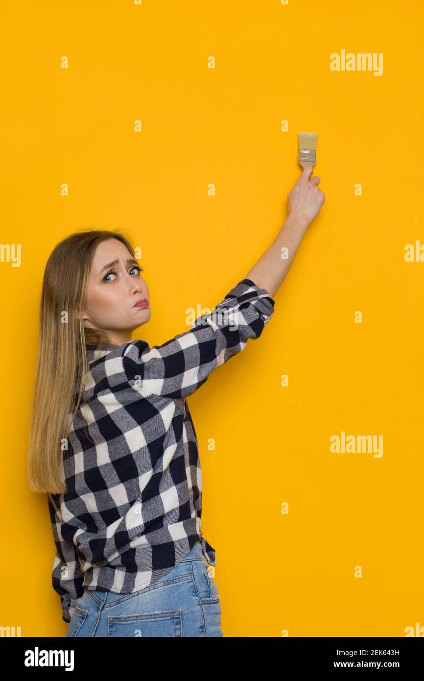 Worried young blond woman in lumberjack shirt and jeans is painting yellow wall with brush and looking at camera over the shoulder. Waist up shot. Stock Photo