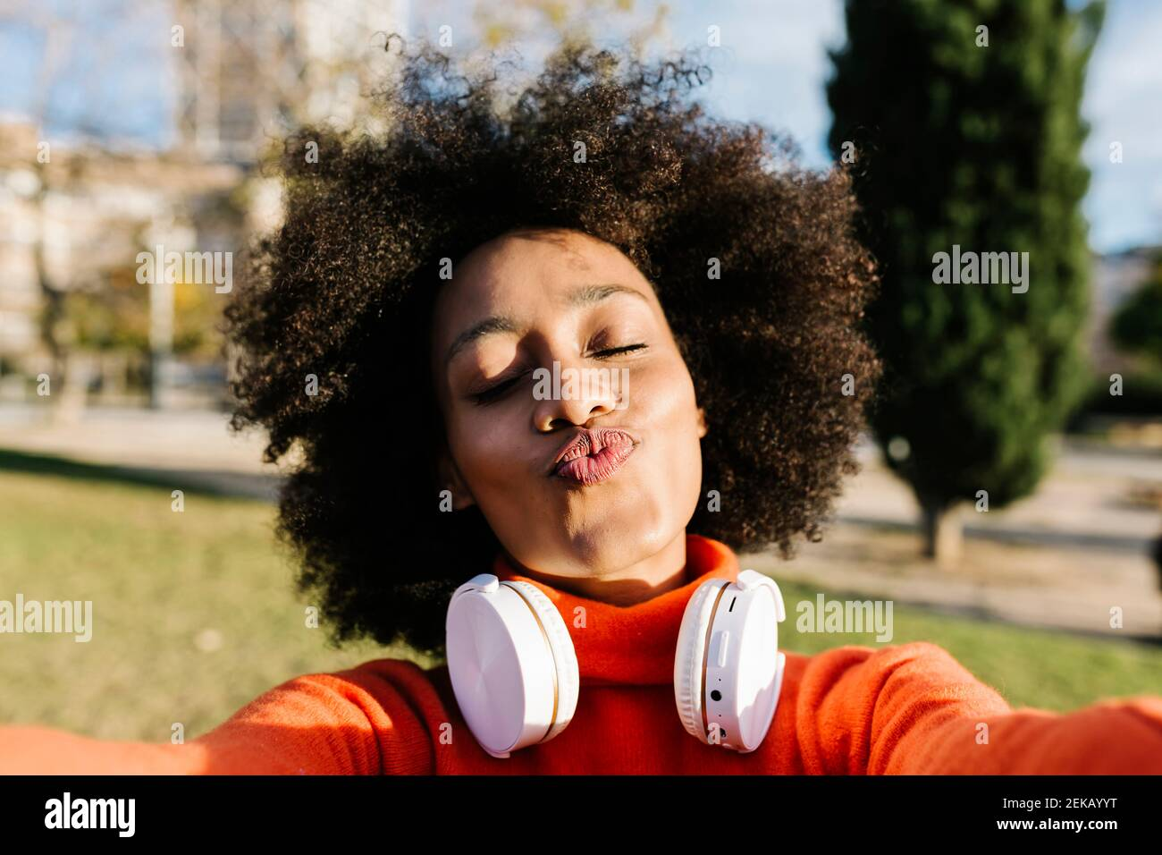 Young woman with eyes closed puckering while taking selfie at park Stock Photo