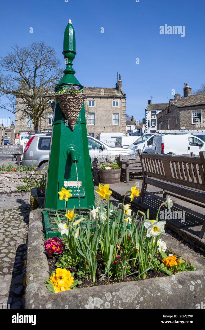Spring view of the painted old water pump and trough, filled with flowers in Grassington, North Yorkshire Stock Photo