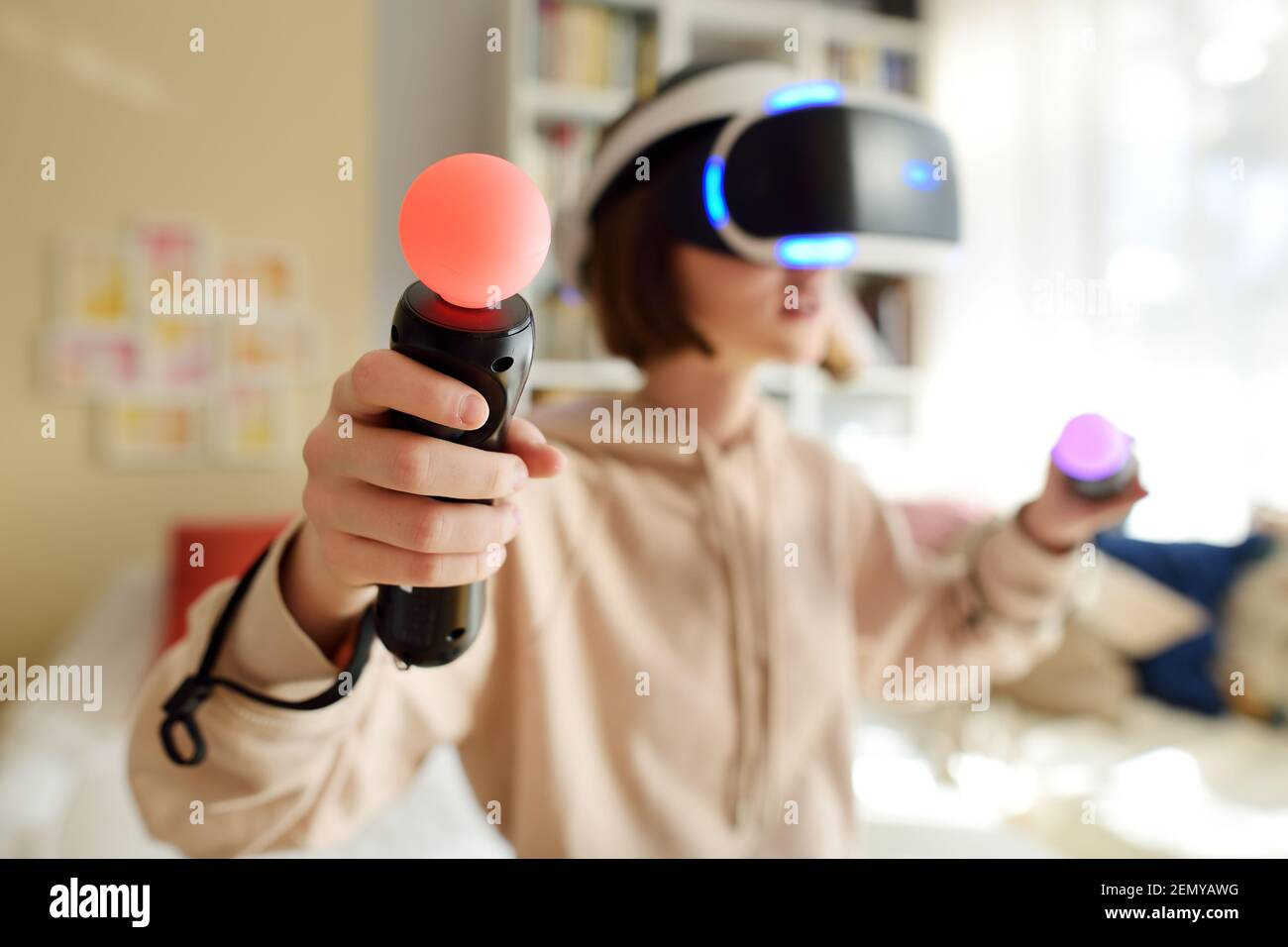 Pretty teenage girl wearing virtual reality headset at home. Cute teen using VR glasses to play a game. Child in virtual augmented reality helmet. Fut Stock Photo